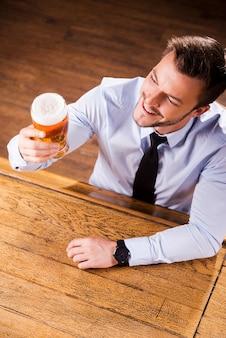 町で最高のビールを楽しんでいます。シャツとネクタイのハンサムな若い男の上面図は、ビールとガラスを調べて、バーのカウンターに座って笑っている