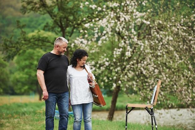 페인트를 즐기고 있습니다. 사랑스러운 성숙한 부부는 여가 시간에 공원에서 산책을