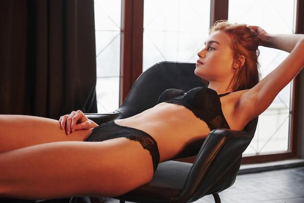 Наслаждаясь отдыхом. горячая великолепная молодая девушка в нижнем белье сидит на стуле в помещении