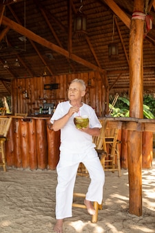 退職後の楽しみ。幸せな年配の男性がビーチ バーでココナッツ ウォーターを飲んでいます。