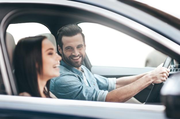 여행을 즐기고 있습니다. 운전대에 손을 잡고 있는 잘생긴 남자가 차에 앉아 웃고 있는 젊은 부부
