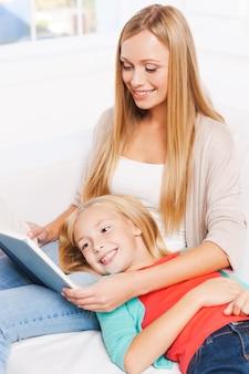 Наслаждаемся своей любимой книгой вместе. вид сверху счастливой матери и дочери, читающей вместе, сидя на диване дома вместе