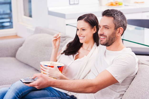Enjoying their favorite show. beautiful young loving couple bonding to each other and eating popcorn while sitting on the couch and watching tv