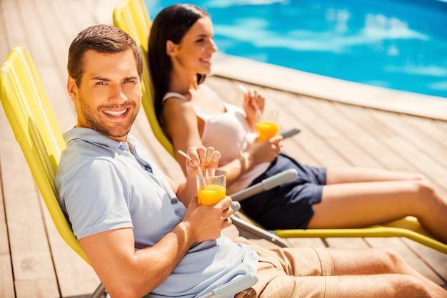 Наслаждаемся своим досугом вместе. вид сбоку красивой молодой пары, сидящей на шезлонгах у бассейна и пьющей коктейли, пока мужчина смотрит в камеру и улыбается