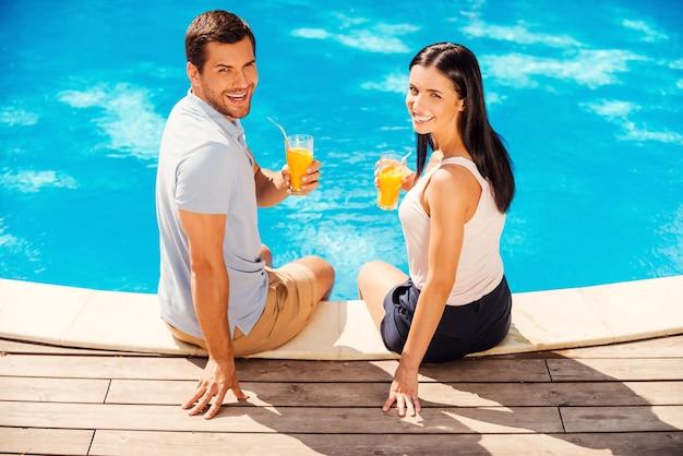 Наслаждаясь летними каникулами. вид сверху счастливой пары в повседневной одежде, держащей очки с апельсиновым соком и улыбающейся, сидя у бассейна вместе