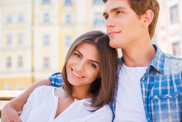 Наслаждаемся временем вместе. красивая молодая влюбленная пара, сидя на скамейке вместе, пока женщина смотрит в камеру и улыбается