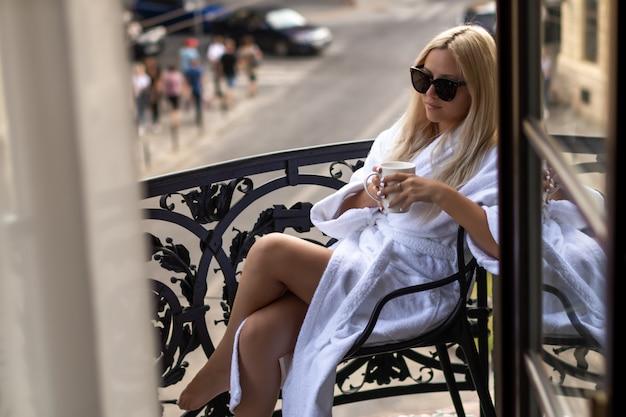 自宅で時間を楽しんでいます。自宅のバルコニーに座って温かい飲み物を歌っている白いバスローブで朝の美しい少女