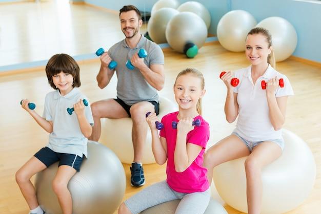 일종의 클럽에서 시간을 즐기고 있습니다. 함께 피트니스 공에 앉아있는 동안 스포츠 클럽에서 아령으로 운동하는 행복한 스포티 한 가족의 상위 뷰