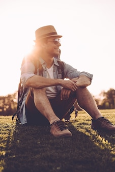 新鮮な空気の中で時間を楽しんでいます。バックパックを背負って、屋外の緑の芝生に座って笑っているフェドーラのハンサムな若い男