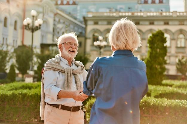 晴れた日に屋外で笑顔で踊る美しい年配のカップルと一緒に時間を楽しんでいます