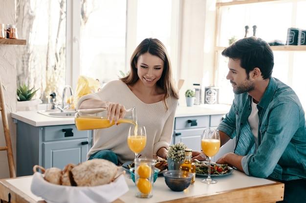 함께 시간을 즐기고 있습니다. 집에서 부엌에 앉아있는 동안 건강한 아침 식사를 즐기는 아름다운 젊은 부부