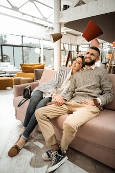 一緒に時間を楽しんでいます。買い物の結果に満足している彼らの顔に広い笑顔で座っている優秀な美しいカップル