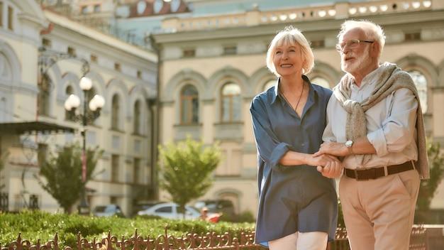 Наслаждаемся временем вместе счастливая и красивая пожилая пара, держась за руки во время прогулки на свежем воздухе