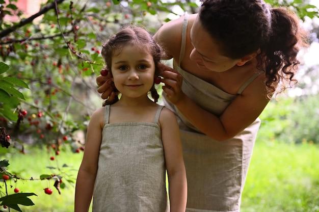 一緒に時間を楽しんでいます。幸せな家族。ポジティブな人間の感情。さくらんぼの収穫期に一緒に素敵な時間を過ごしているママと娘。ママは娘の耳にチェリーベリーのイヤリングをつけます。