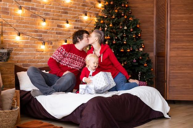休日に一緒に時間を楽しんでいます。家でクリスマスツリーの近くで楽しんでいる幸せな母、父と小さな子供