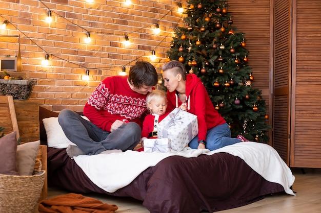 休日に一緒に時間を楽しんでいます。幸せな母、父と家のクリスマスツリーの近くの小さな子供