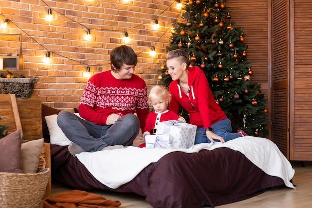 休日に一緒に時間を楽しんでいます。クリスマスツリーの近くで幸せな母、父と小さな子供。