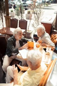 함께 시간을 즐기고 있습니다. 레스토랑 밖에 앉아 함께 시간을 즐기는 회색 머리 남자의 상위 뷰
