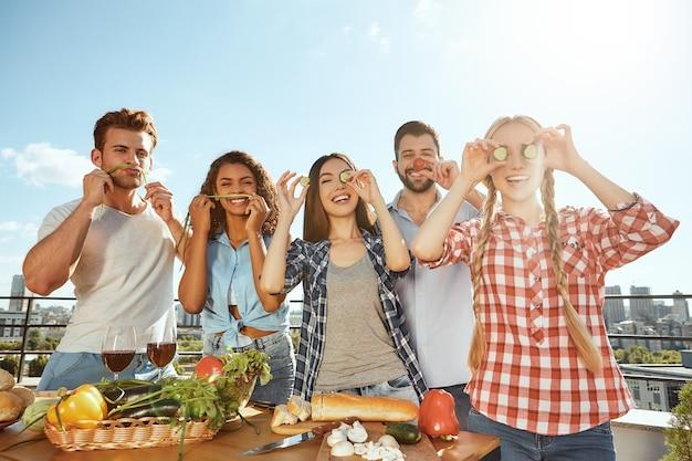 캐주얼 옷을 입고 음식을 준비하는 젊고 쾌활한 친구들과 즐거운 시간