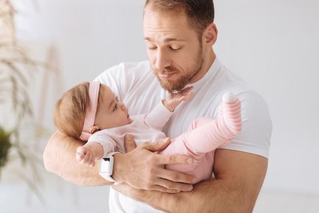 赤ちゃんとの時間を楽しんでいます。家に立って、ケアと愛を表現しながら幼児の女の子を腕に抱いて、うれしそうなカリスマ的なひげを生やした父親