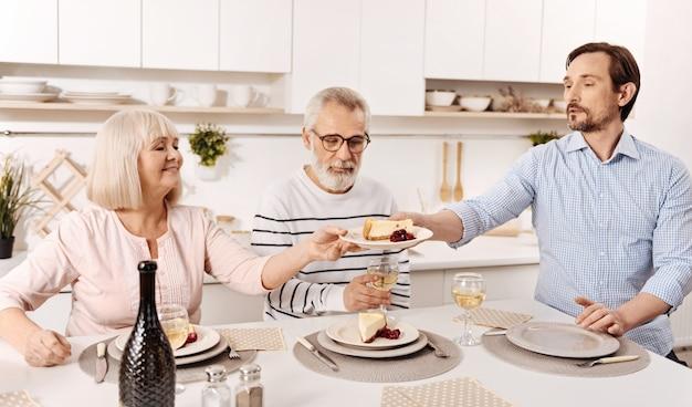 伝統的な家族の夕食を楽しんでいます。楽観的な成熟した男性が夕食をとり、母親からデザートのプレートを手に入れながら、先輩の両親と週末を楽しんでいる