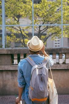 旅行を楽しんでいます。アジアのストリートでカメラを保持しているバックパックを持つ若い笑顔の男。