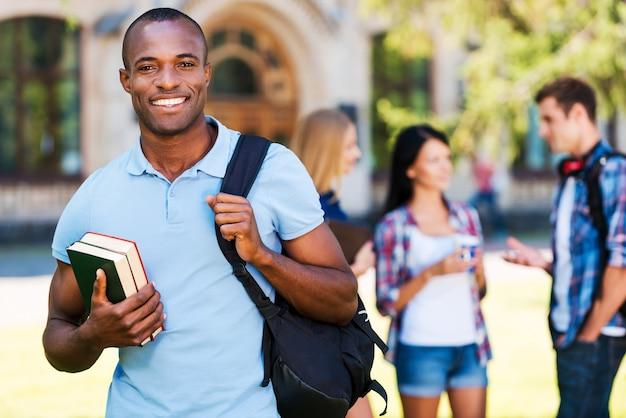 大学生活を楽しんでいます。本を持って、バックグラウンドでチャットしている彼の友人と大学に立ち向かいながら笑っているハンサムな若いアフリカ人