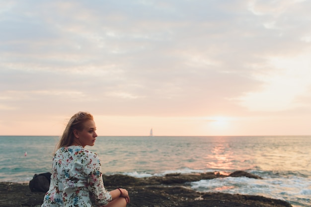 Enjoying vacation. young traveling woman enjoying sunset on sea view point.