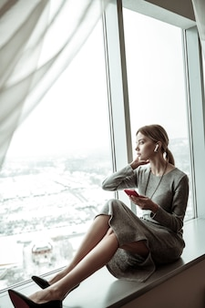 Enjoying the view. slim stylish woman sitting near window and enjoying the view from her apartment