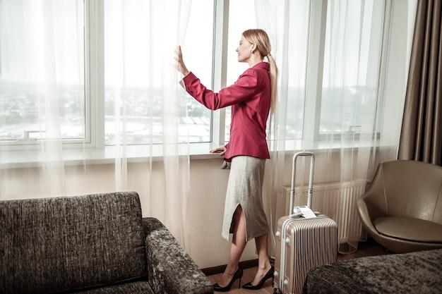 窓の眺めを楽しんでいます。ホテルからの窓の眺めを楽しむ出張で金髪のスタイリッシュな女性