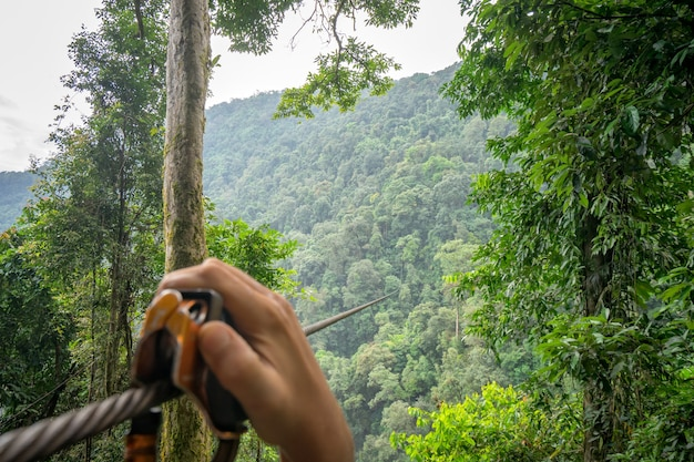 Enjoying with a zipline adventure across the mountain for watch the scenery of the sky and