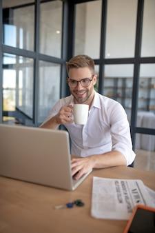仕事を楽しんでいます。コーヒーを飲んで作業タスクを解決する笑顔の男