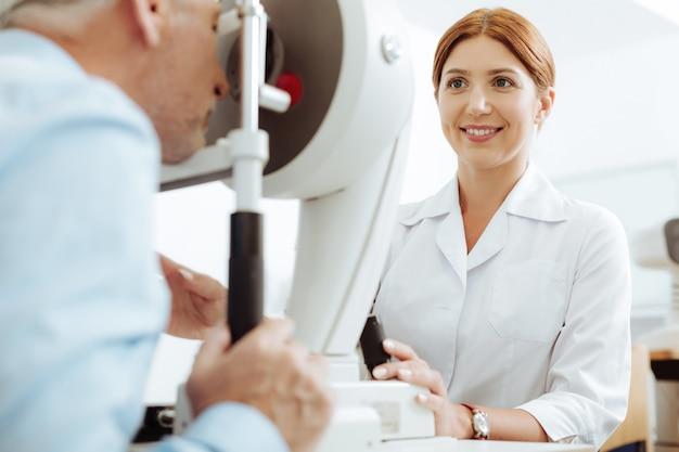 Наслаждаюсь работой. рыжий улыбающийся глазной врач в униформе наслаждается процессом работы