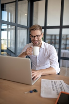 Enjoying work. a smiling man having coffee and solving working tasks