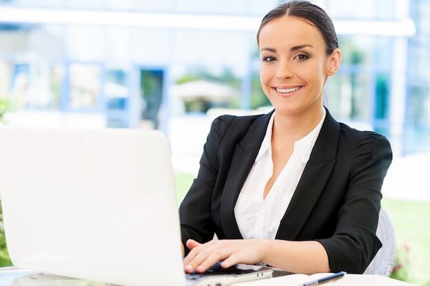 야외에서 일하는 것을 즐깁니다. 야외 테이블에 앉아 노트북 작업을 하고 웃고 있는 정장 차림의 매력적인 젊은 여성
