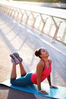ヨガのトレーニングを楽しんでいます。外のスポーツマットでヨガのトレーニングを楽しんでいる浅黒い肌の女性のトップビュー