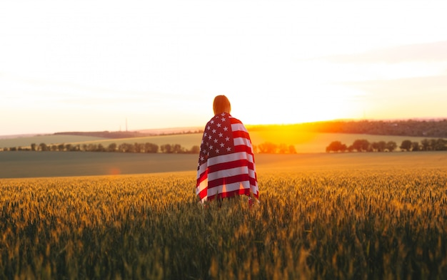 Enjoyng woman with american flag in a wheat field at sunset. 4th of july.  independence day, patriotic holiday.