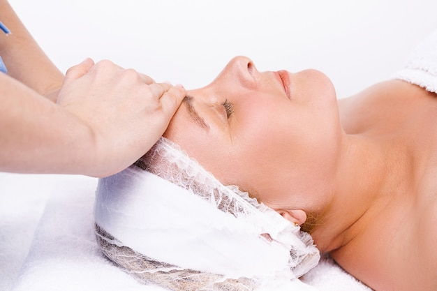 Enlarged photo. the hands of the master massage the face of an older woman. white background.