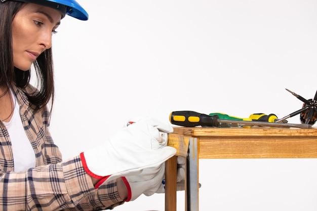 ドライバーでスツールを修理する女性の建設労働者の拡大写真白い孤立した背景