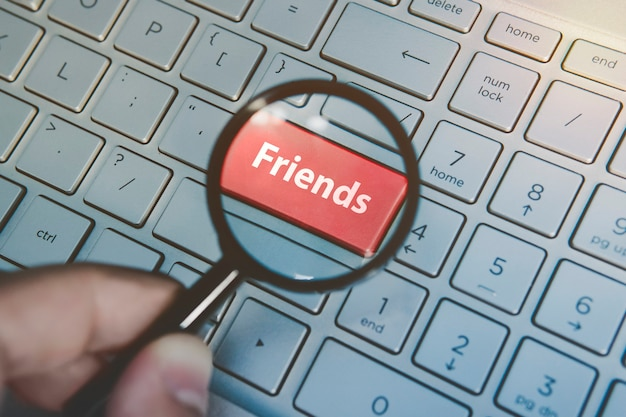 Увеличено через увеличительное стекло красный ключ друзья на фоне клавиатуры. онлайн поиск друзей. человек ищет друзей в интернете. поиск друзей в социальных сетях. виртуальные друзья.