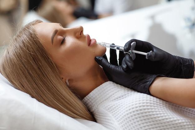 Увеличение, коррекция губ. портрет белой женщины во время операции заполнения морщин на лице. пластическая хирургия. молодая женщина, получающая косметические инъекции