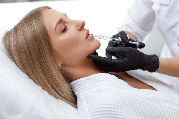입술 확대, 입술 교정. 얼굴 주름을 채우는 작업 중 세로 백인 여자. 성형 수술. 입술에 화장품 주입을 받고 젊은 여자
