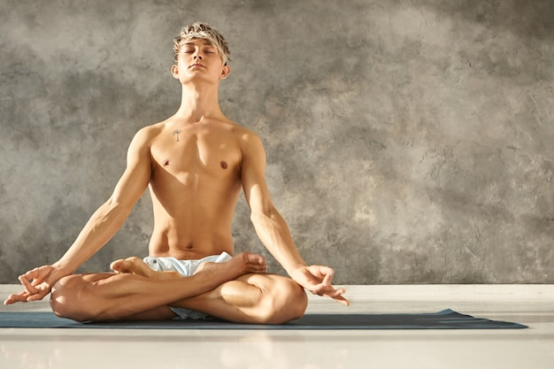 Enlightened young caucasian man posing shirtless and barefooted at gym, having calm peaceful facial expression, meditating with eyes closed, sitting on mat in lotus pose, hands in mudra gesture