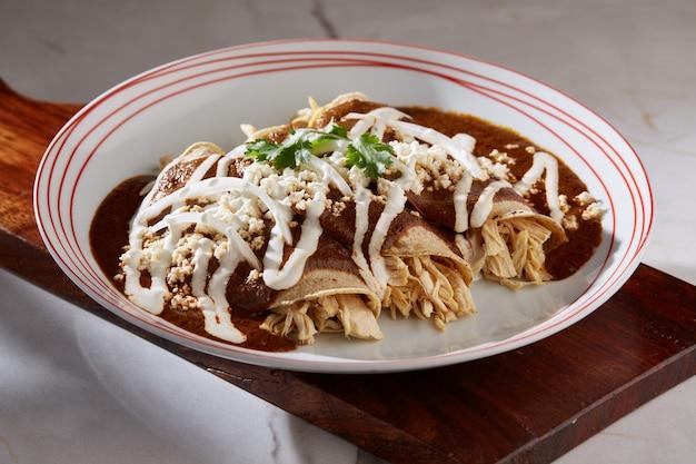 Enmoladas de pollo comida typeica mexicana tortilla de maiz rellena de pollo cubiertas de mol