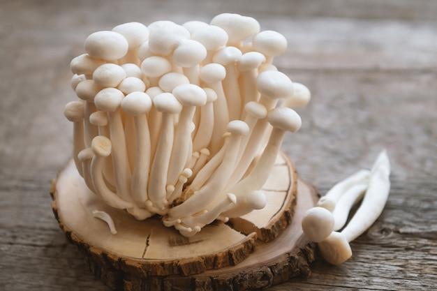 나무 테이블에 팽이 버섯을 닫습니다.