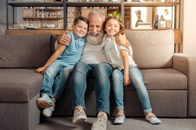 とてつもない愛。ソファに座って愛する孫を抱きしめながら、みんなが笑顔で一緒にいて幸せな愛情のこもった年配の男性