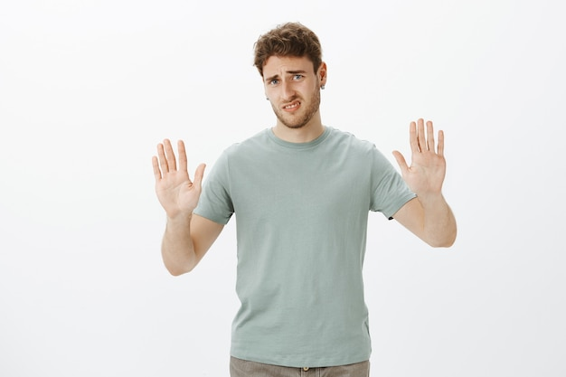 Enough, do not bother me. displeased and disgusted charming man in t-shirt, pulling hands towards in rejection gesture