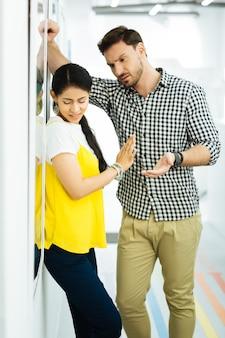 충분히. 지친 긴장된 소녀는 눈을 감고 한 손을 들고 무례한 뻔뻔스러운 남자 친구가 한 걸음 더 나아가 그녀와 이야기하는 것을 막습니다.