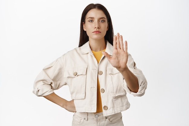 Enough, keep distance. serious girl extend hand in taboo, stop sign, say no to smth bad, prohibit or restrict smth, rejecting offer, standing  on white