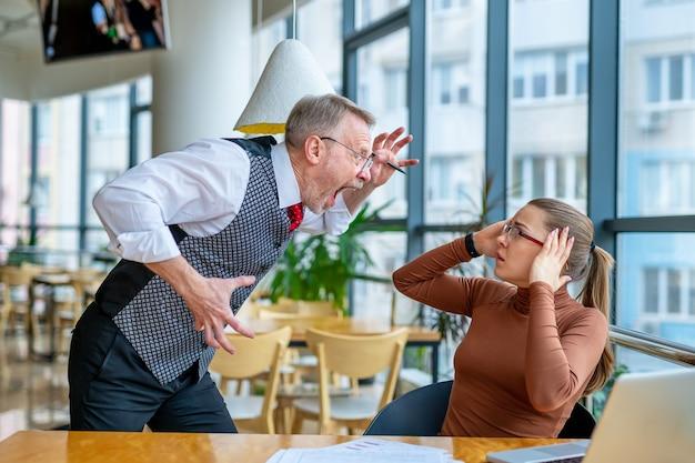 화가 난 사업가는 현대 사무실에서 좌절한 소녀에 대한 작업에 불만을 표시합니다.
